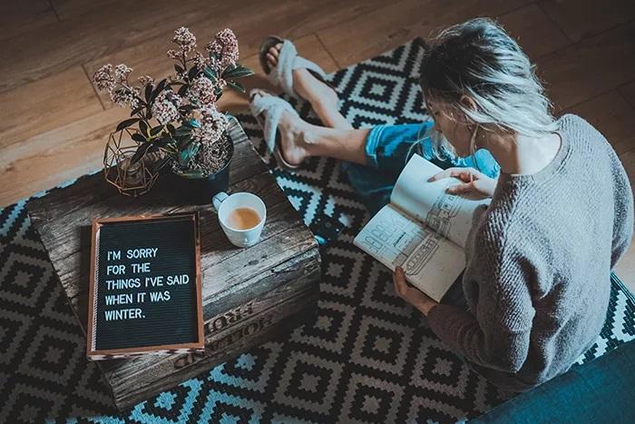 پرتره دنج یک مدل زن که در داخل خانه نشسته است - ایده های عکاسی زمستان